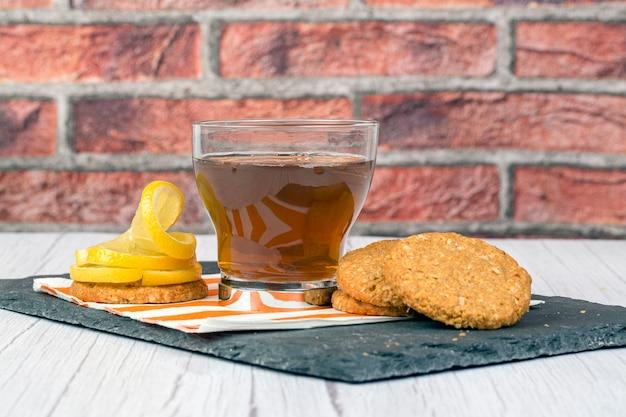 Galletas de avena taza de té y rodajas de limón sobre placa de piedra y fondo de ladrillo.