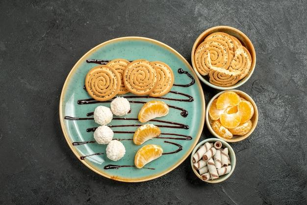 Galletas de azúcar de vista superior con caramelos de coco sobre fondo gris