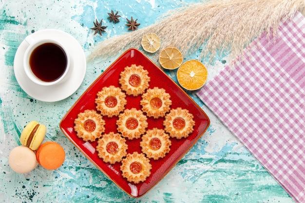 Galletas de azúcar de vista superior con taza de té y macarons en el fondo azul