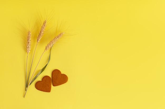 Galletas con canela en forma de corazón, espigas de trigo superficie amarilla