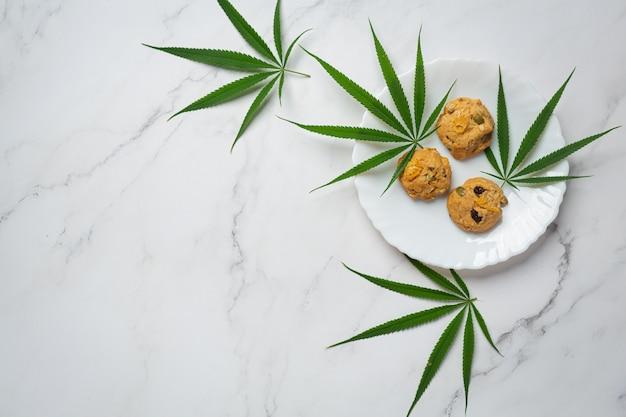 Galletas de cannabis y hojas de cannabis en placa blanca.
