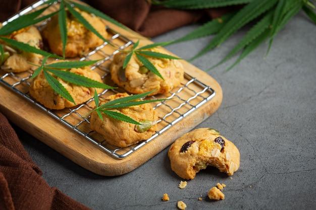 Galletas de cannabis y hojas de cannabis en tabla de cortar de madera