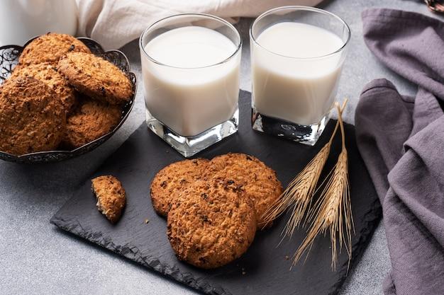 Galletas caseras, cereales, avena y un vaso de leche sobre la mesa de hormigón gris.