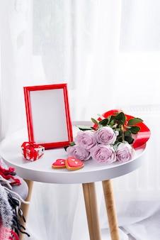 Galletas caseras del corazón del día de san valentín, rosas rosadas y marco rojo en la mesa blanca cerca de la ventana