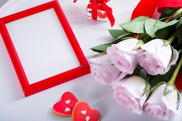 Galletas caseras del corazón del día de san valentín, rosas rosadas y marco rojo en la mesa blanca