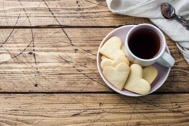 Galletas caseras del corazón y taza de café en una placa