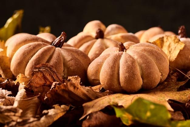 Galletas caseras en forma de calabaza en hojas de otoño. galletas hechas a mano de halloween en una mesa, de cerca