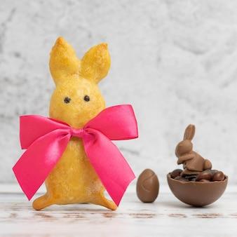 Galletas caseras con forma de conejo con lazo rojo y huevo de chocolate en una luz.