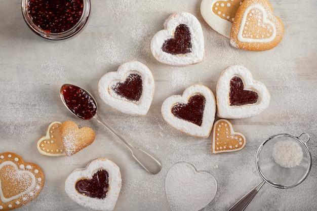 Galletas caseras en forma de corazón con mermelada de frambuesa en mesa de madera blanca para navidad o san valentín. vista superior.