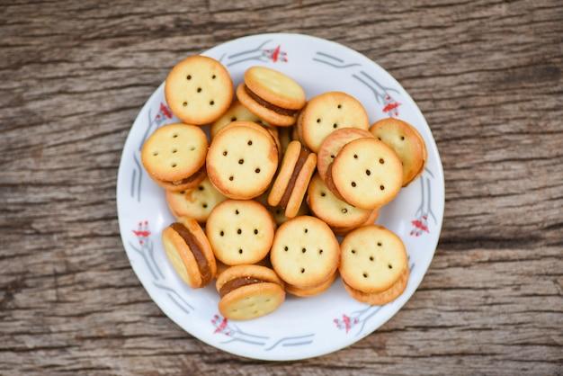 Galletas caseras con mermelada de piña en la mesa de madera - galletas de galletas en un plato para galletas saladas
