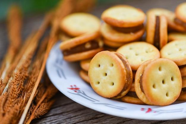 Galletas caseras con mermelada de piña en la mesa de madera, galletas de galletas en un plato para galletas saladas