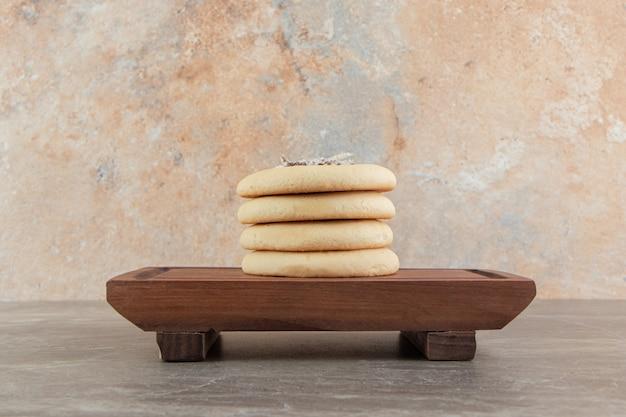 Galletas caseras rellenas de chocolate sobre tabla de madera