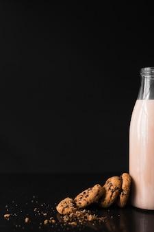 Galletas cerca de la botella de leche sobre fondo negro