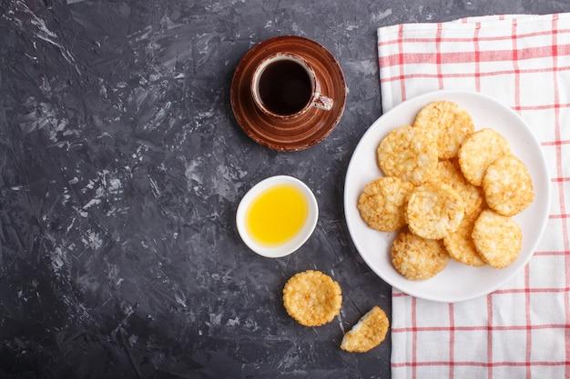 Galletas de chips de arroz japonés tradicional con miel y salsa de soja en un plato de cerámica blanca y una taza de café