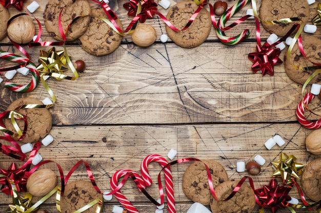 Galletas con chispas de chocolate bastones de navidad caramelo oro rojo paisaje y malvavisco en madera. copyspace marco.