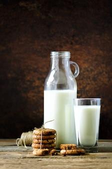 Galletas con chispas de chocolate, botella y vaso de leche.