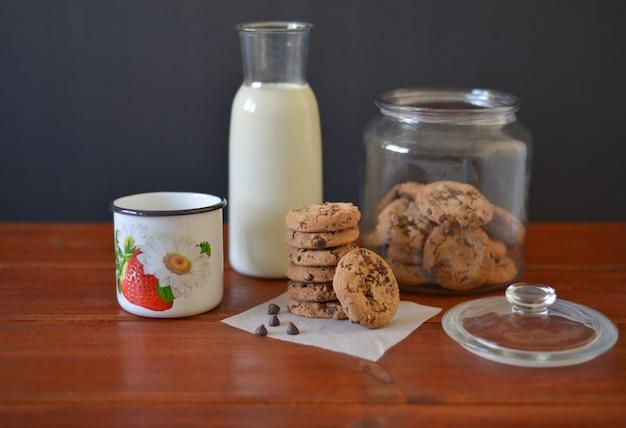 Galletas con chispas de chocolate en un frasco de vidrio con una botella de vidrio de leche y una taza de esmalte blanco sobre fondo rústico de madera