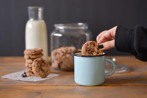 Galletas con chispas de chocolate en un frasco de vidrio con una botella de vidrio de leche y una taza de esmalte turquesa sobre un fondo rústico de madera con una mano de mujer sosteniendo una galleta