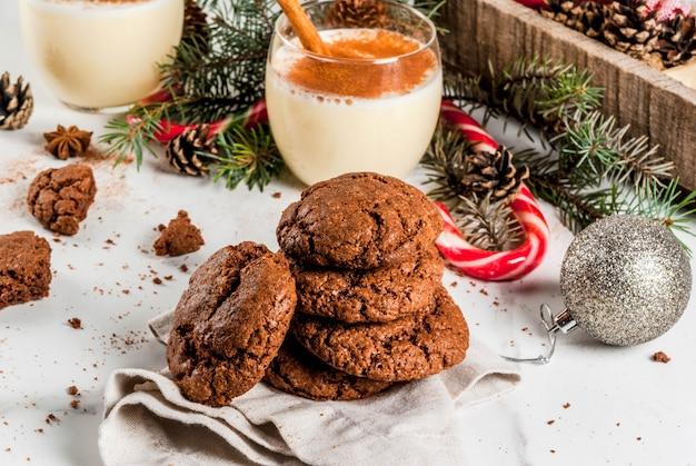 Galletas de chocolate arrugadas para navidad, con cóctel de ponche de huevo, bastón de caramelo, árbol de navidad y decoración navideña, en mesa de mármol blanco
