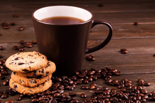 Las galletas de chocolate están parados antes de la taza de café