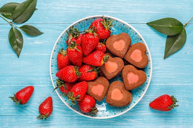 Galletas de chocolate y fresa en forma de corazón con fresas frescas, vista superior