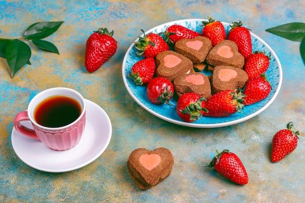 Galletas de chocolate y fresa en forma de corazón con fresas frescas