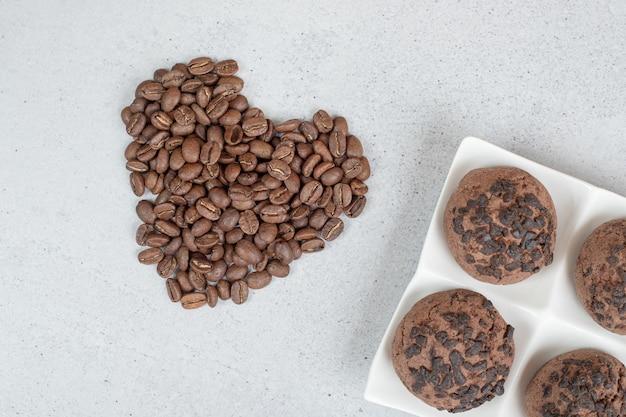 Galletas de chocolate con granos de café sobre superficie blanca.