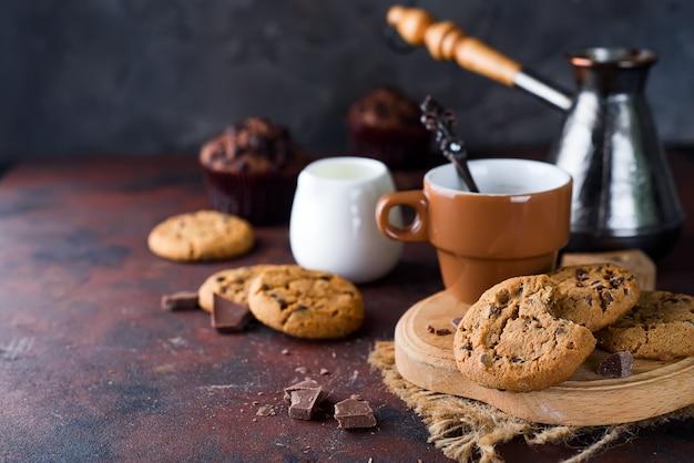 Galletas de chocolate en un plato y una taza de café caliente en la mesa de piedra