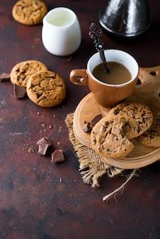 Galletas de chocolate en plato y taza de café caliente