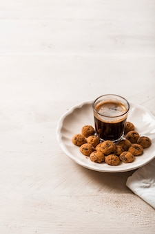 Galletas de chocolate con vaso de café espresso sobre fondo de madera