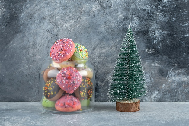 Galletas de colores con chispitas en tarro de cristal y pino.
