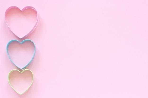Las galletas coloridas de los cortadores en forma del corazón en fondo rosado en colores pastel