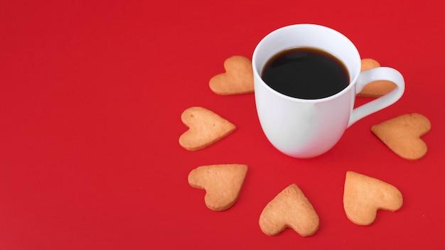 Galletas de corazón con taza de café blanco en la mesa