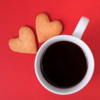 Galletas de corazón con taza de café en la mesa roja