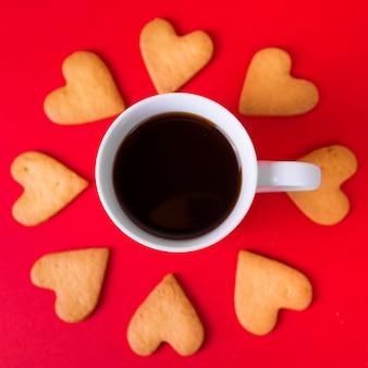 Galletas de corazón con taza de café en la mesa