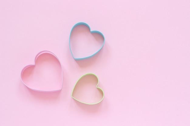 Las galletas de los cortadores de colorfed en corazón forman en fondo rosa en colores pastel. tarjeta de san valentín concepto.