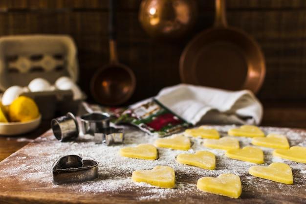 Galletas crudas y cortadores en la cocina