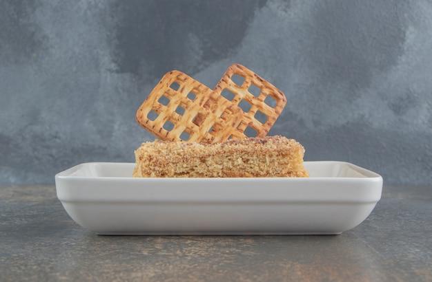 Galletas decoradas con una rebanada de pastel en un plato