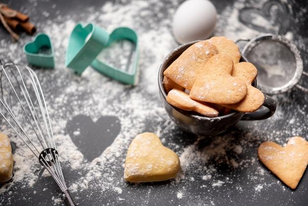 Galletas del día de san valentín con harina y utensilios de cocina.