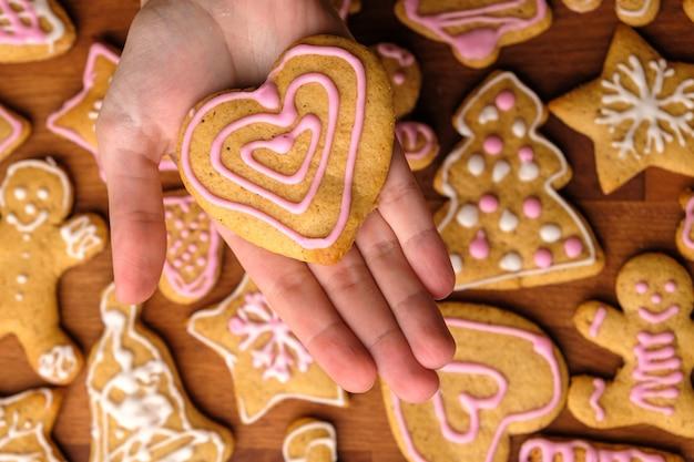 Galletas para el día de san valentín en manos de mujer en el fondo de pan de jengibre.