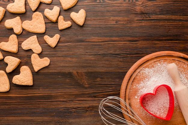 Galletas del día de san valentín con utensilios de cocina sobre fondo de madera