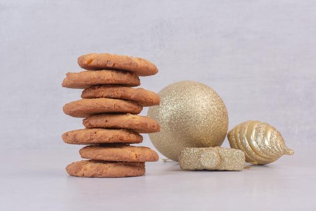 Galletas dulces con bolas de navidad doradas sobre superficie blanca