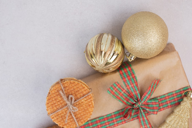 Galletas dulces en cuerda con regalo y juguete dorado de navidad sobre superficie blanca