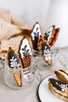 Galletas dulces en forma de helado en frasco de vidrio sobre una mesa.