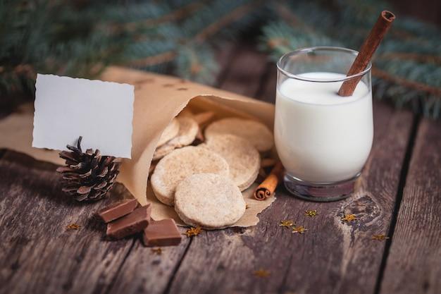 Galletas dulces de navidad con leche en escritorios de madera