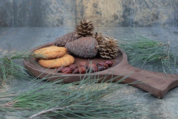 Galletas, escaramujos secos y piñas sobre tabla de madera. foto de alta calidad
