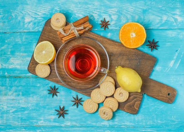 Galletas con especias, té, limón, naranja sobre azul y tabla de cortar