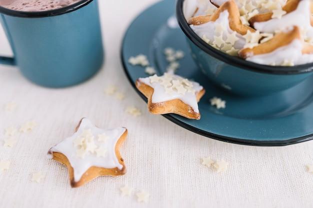 Galletas estrella en un tazón con taza de cacao