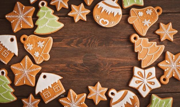 Las galletas festivas del pan de jengibre de la navidad en la forma de una estrella mienten en un fondo de madera del marrón oscuro.