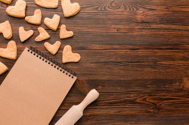 Galletas en forma de corazón para el día de san valentín con cuaderno y rodillo